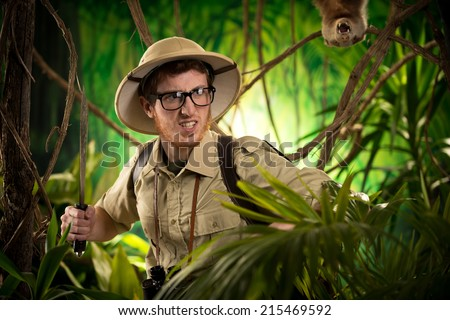 Aggressive confident explorer walking in the jungle holding a machete with ferocious animal on background. - stock photo