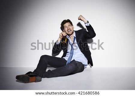 Aggressive drunk businessman shaking fist in studio