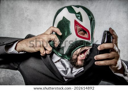 aggressive executive suit and tie, Mexican wrestler mask - stock photo