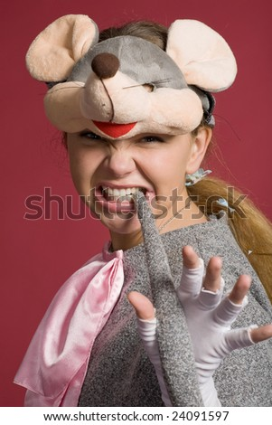 aggressive girl in  mouse suit holds  tail in  teeth on red background