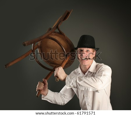 aggressive guy with chair on dark background - stock photo