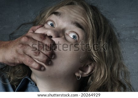 Aggressive hand closing mouth of the victim - stock photo