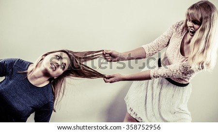 Aggressive mad women fighting each other pulling hair. Two young girls struggling win catfight. Violence. - stock photo