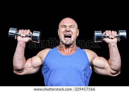 Aggressive man lifting dumbbells against black background - stock photo