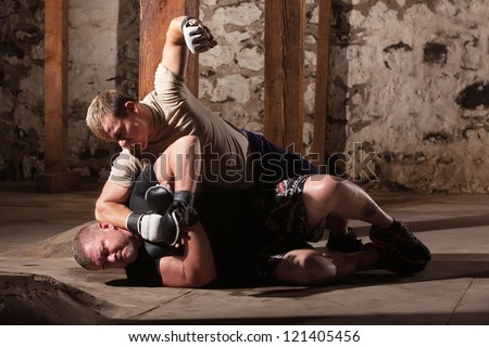 Aggressive MMA fighter punching opponent on the ground - stock photo