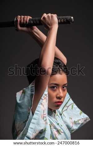 Aggressive move. Side view portrait of young beautiful Japanese woman in kimono attacking with katana sword while standing against grey background - stock photo