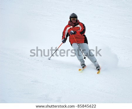 Aggressive sport skier in the snow powder skiing fast