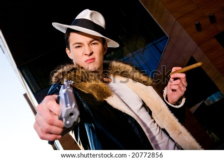 Aggressive young gangster with a gun and cigar aiming at camera outdoors - stock photo