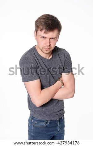 Aggressive young man, arms folded, isolated on white