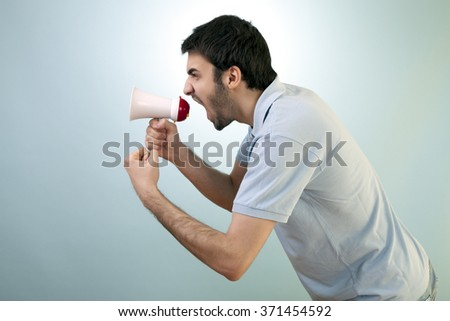 Aggressive young man is shouting out loud to protest something over a megaphone against blue background.