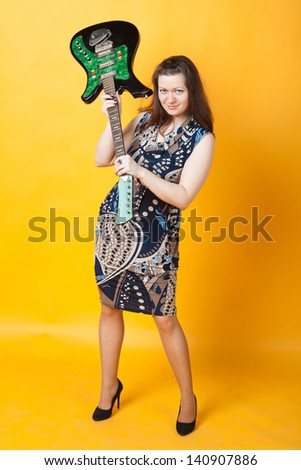 aggressive young woman staying with electric guitar - stock photo