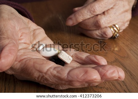 Aging and Health Care - hands and pills  - stock photo