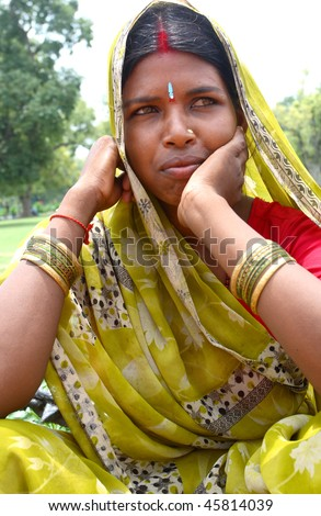 AGRA, INDIA - JUNE 19: Portrait of happy tribal woman in a city in India, Agra June 19, 2008 in Agra, India. Local women wear colorful saree (sari) as traditional clothing. - stock photo