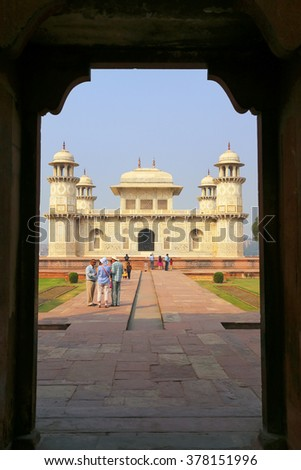 AGRA, INDIA - NOVEMBER 6: Unidentified people walk near Itimad-ud-Daulah Tomb on November 6, 2014  in Agra, India. This Tomb is often regarded as a draft of the Taj Mahal. - stock photo