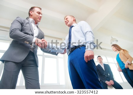 Agreement and partnership. Two confident businessmen shaking hands with colleagues talking in the background. Indoors. - stock photo