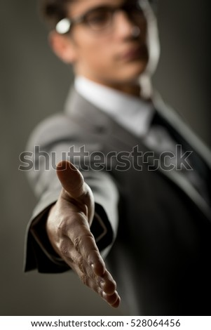 agreement or welcome concept with a hand reaching out from the blurred background of a young man