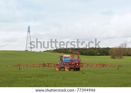 agricultural crop sprayer in action under a cloudy sky - stock photo