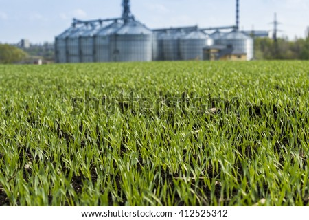 Agricultural grain elevator near field - stock photo