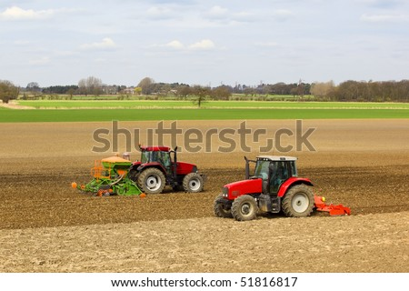 agricultural landscape with two red tractors cultivating and sowing spring barley in springtime - stock photo