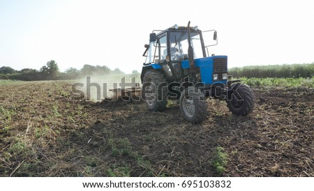Agricultural tractor sowing and cultivating field at organic eco farm. real working process at small family farm.