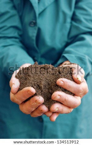 Agricultural worker holding a soil in cupped hands. Spring, growth, new life, ecology, environmental, nature preservation concept - stock photo