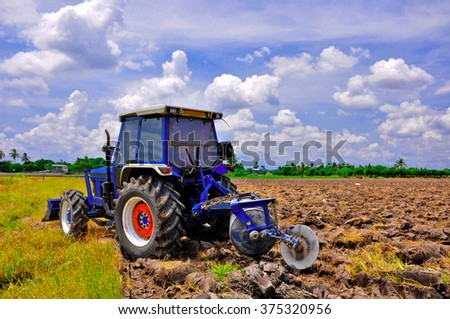 Agriculture plowing tractor on wheat cereal fields moving ,farmer job - stock photo