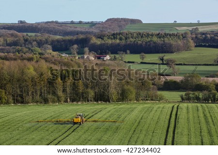 Agriculture - Spraying fertilizer on wheat crop in the North Yorkshire countryside - England. - stock photo
