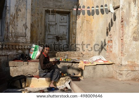 AHMADABAD, GUJARAT, INDIA - JANUARY 26: Shoemaker fixing shoes in streets of Indian cities in the Gujarat state in India, Ahmadabad in January 28, 2015