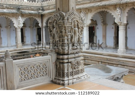 AHMEDABAD, GUJARAT, INDIA - AUGUST 21 : Hutheesing Jain Temple on August 21, 2012 in Ahmedabad. Sculpture of Jain deity on the column of the main entrance. Colanneded corridor in backdrop. - stock photo