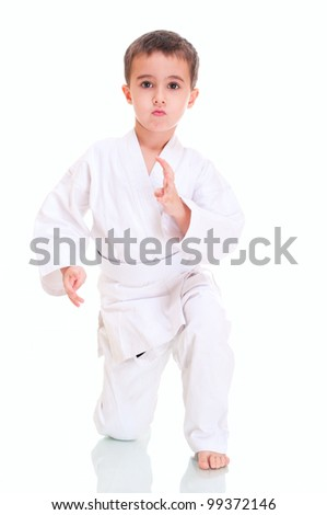 Aikido boy fighting position on a knee in white kimono isolated on white