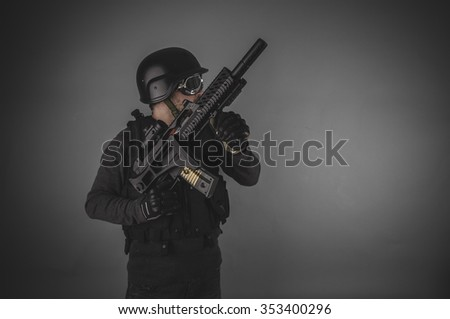 aiming, airsoft player with gun, helmet and bulletproof vest on gray background - stock photo