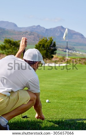 aiming golfer lining putt on green - stock photo