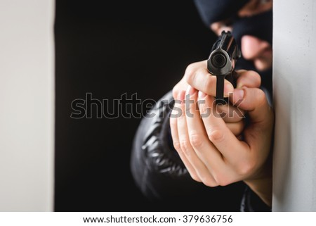 Aiming murderer with a gun - stock photo