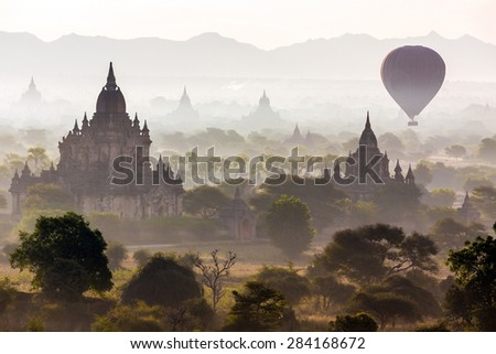 Air balloons flying over pagodas at misty dawn in the plain of Bagan, Myanmar (Burma) - stock photo