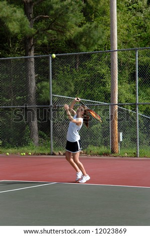 Air born ball keeps the eye of tennis player as she swings her tennis racket to connect. - stock photo