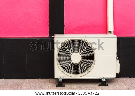 Air compressor located outside home near pink wall - stock photo