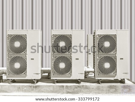 Air compressor on concrete pedestal  with siding wall background. - stock photo