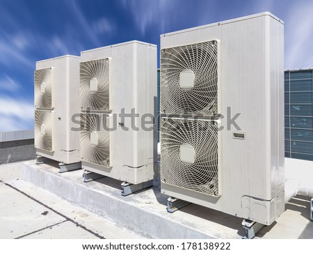 Air compressor on roof of factory with blue sky background. - stock photo