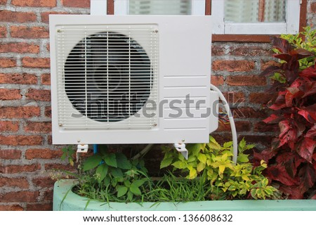 air compressor on the brick wall - stock photo