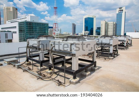 Air compressor on the Building office in city with blue sky background. - stock photo