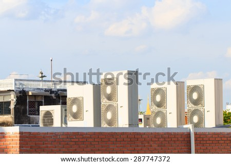 Air condition compressor on roof with blue sky background - stock photo