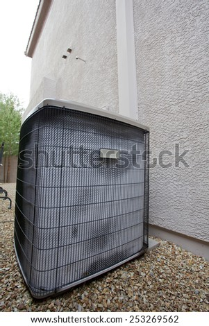 Air conditioner external compressor heat exchange unit (also referred as Heat Pump) covered with white frost in the backyard on cold and humid January morning - stock photo