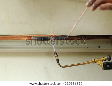 Air conditioner repairman welding copper pipes - stock photo