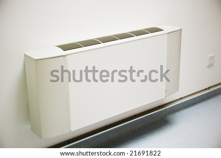 air-conditioner unit on white wall - stock photo