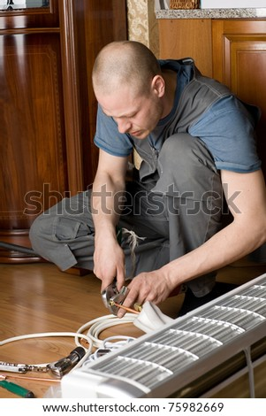 Air conditioning master prepares a new air conditioner to be installed in the apartment. - stock photo