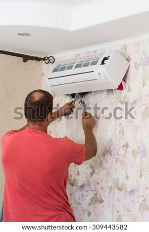 Air conditioning master preparing to install new air conditioner. - stock photo