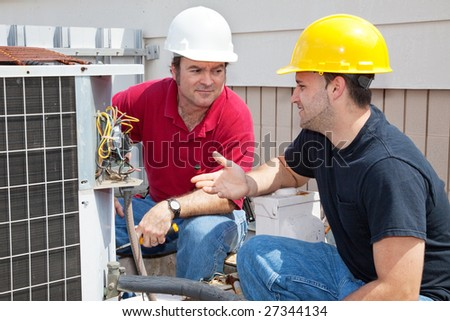 Air conditioning repairmen discussing the problem with a compressor unit. - stock photo