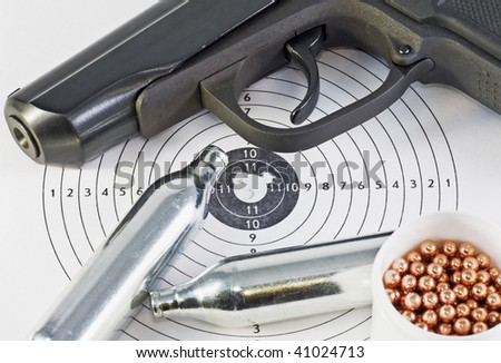 air pistol and spare parts for weapons lie on the hole in the target - stock photo