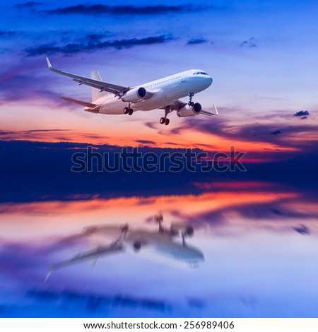 air plane flying on the sea at dusk - stock photo