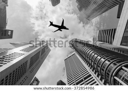 Air plane flying over the high buildings in central business district. - stock photo